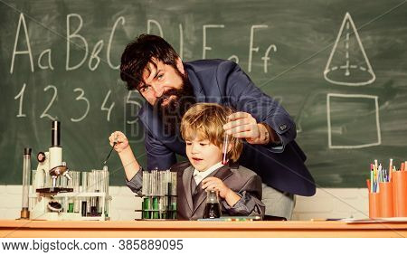 Using Microscope In Lab. Father And Son At School. Student Doing Science Experiments With Microscope