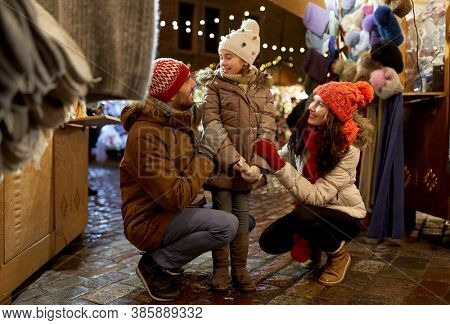 family, winter holidays and celebration concept - happy mother, father and little daughter at christmas market on town hall square in tallinn, estonia