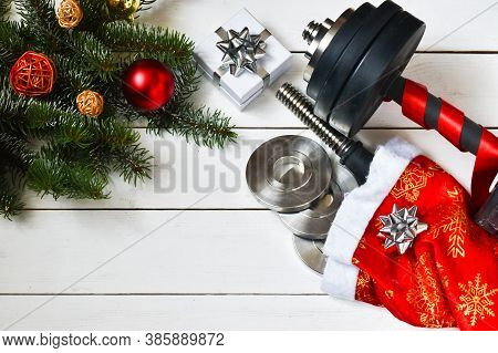Cristmas Sports. Black Sport Dumbbells, Gifts And Bows On Wooden White Background. Merry Christmas A