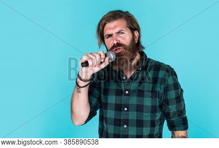 Guy With Beard Singing In Microphone. Confidence And Charisma On Stage. Bearded Man Wearing Checkere