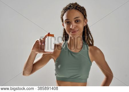 Close Up Of Young Happy Mixed Race Fitness Woman Holding Bottle With Sports Nutrition Supplements An