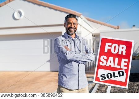Portrait of confident indian man with crossed arms standing near sold signboard outside new home. Successful mixed race real estate agent purchasing new home for investment purpose with copy space.