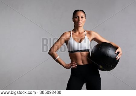 Portrait of beautiful mid adult woman looking at camera while holding heavy medicine ball isolated on grey background. Strong woman holding sports ball after cross training workout with copy space.