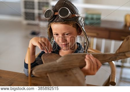 Boy wearing pilot helmet playing with vintage wooden airplane at home. Happy child playing with wooden flight simulator. Little boy holding handmade plane with pilot cap and goggles at home.
