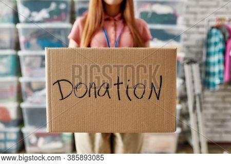 Close Up Of Box For Donation, Young Woman Volunteer Holding Cardboard Box While Working For A Charit