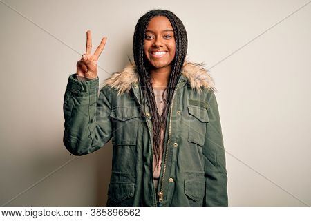 Young african american woman wearing winter parka coat over isolated background showing and pointing up with fingers number two while smiling confident and happy.