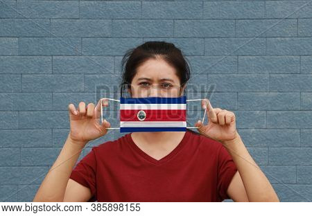 A Woman And Hygienic Mask With Costa Rica Flag Pattern In Her Hand And Raises It To Cover Her Face O