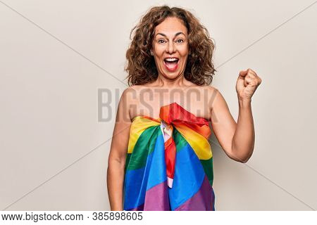 Middle age beautiful woman wearing gay pride flag as a dress over isolated white background screaming proud, celebrating victory and success very excited with raised arm