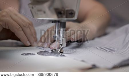 Sewing Striped Shirt On A White Sewing Machine Close Up. Concept Of Sewing In Modern Bright Studio,