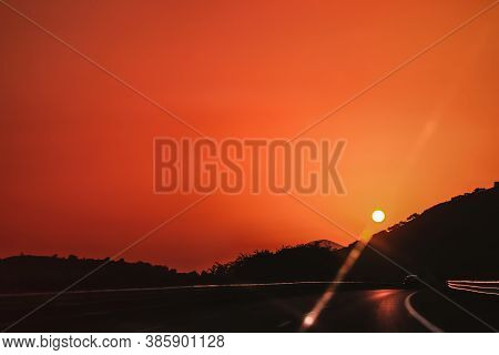 Vibrant Orange Red Deep Colors Sunset Sky Over Highway With One Car Driving And Sun Over Mountains S