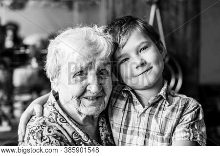 An old woman with her grandson. Black and white portrait.