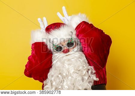 Santa Claus Wearing Glasses With Reindeer Nose And Antlers, Making Funny Faces Isolated On Yellow Co