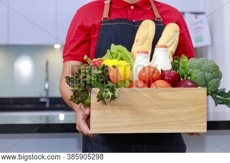 Grocery Delivery Courier Man In Red Uniform With Grocery Box With Fresh Fruit And Vegetable. Deliver