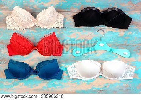 Many Womens Bra And A Hanger On Blue Wooden Background. Underwear Fashion Concept. Basic Lingerie Fl
