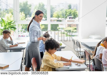 Teacher Standing Near Arabian Schoolboy Writing In Notebook During Lesson