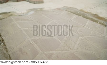 Laying Of Paving Slabs. The Use Of Mortar When Laying Paving Slabs. The Worker Levels The Foundation