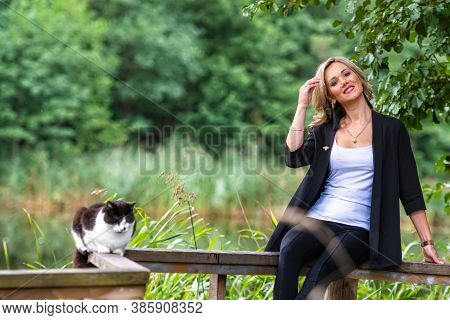Young Blonde Female With Cat Siting On A Railing Wooden Walkway Above The Pound