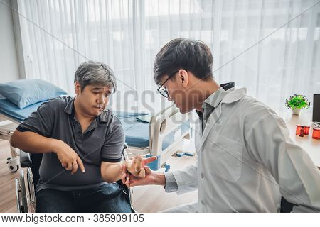 Asian Male Doctor Is Checking The Hand With A Kink Of Middle Aged Male Patients Which Is A Neurologi