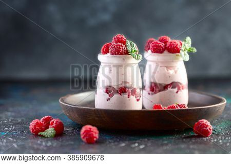 Delicious Homemade Yogurt Served In Glass Jars With Fresh Raspberries And Mint On A Wooden Plate, Se