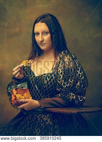 Eating Chips. Young Woman As Mona Lisa, La Gioconda Isolated On Dark Green Background. Retro Style,