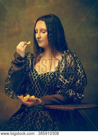 Tastiest Chips. Young Woman As Mona Lisa, La Gioconda Isolated On Dark Green Background. Retro Style