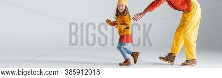 Partial View Of Mother And Daughter In Colorful Red And Yellow Outfits Running On Grey Background, P