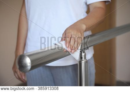 Woman Cleaning Metal Railing With Tissue Paper, Closeup