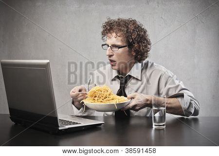 Businessman surprising while using a laptop computer and eating spaghetti with tomato sauce