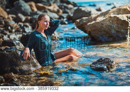 Summer Time And Relaxation Concept. Woman In Blue Wet Dress Sitting In Crystal Sea Water. Meditation