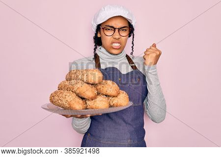 Young african american baker woman wearing apron holding wholemeal bread with cereal annoyed and frustrated shouting with anger, crazy and yelling with raised hand, anger concept