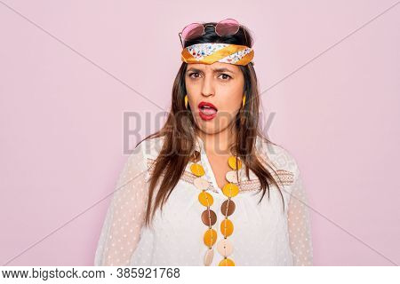 Young hispanic hippie woman wearing fashion boho style and sunglasses over pink background In shock face, looking skeptical and sarcastic, surprised with open mouth