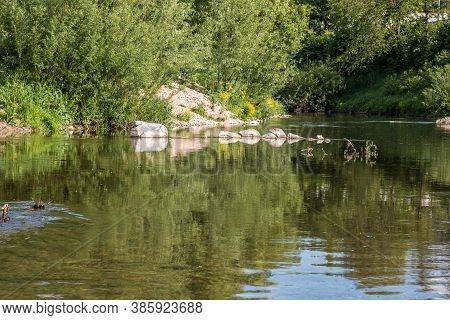 Reflections In The Flowing Water Of The River