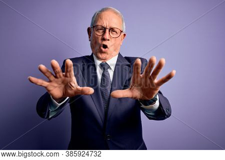 Grey haired senior business man wearing glasses and elegant suit and tie over purple background doing stop gesture with hands palms, angry and frustration expression