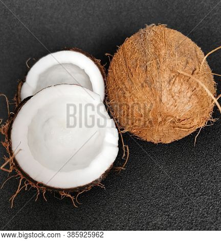 A Whole And A Half Coconut. Vegetarian Food. Coconut On A Black Background.