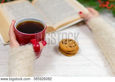 Female Hands With A Cup Of Tea And Cookies On A Wooden Table With A Christmas Tree And Decorations H