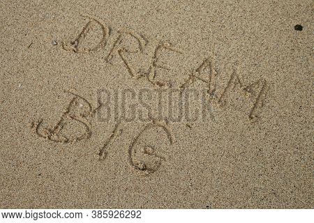 Handwritten Dream Big On A Sandy Sea Beach On A Summer Sunny Day. Disappearing Dreams Concept