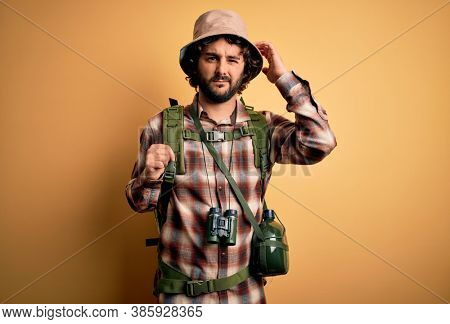 Young hiker man with curly hair and beard hiking wearing backpack and water canteen confuse and wondering about question. Uncertain with doubt, thinking with hand on head. Pensive concept.