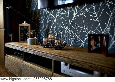 Decorative candlestick, pot flower, portrait images, clock and electronics on wooden furniture surface. Modern living room arrangement. Interior design