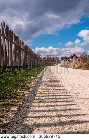 Wooden Fence Along The Stony Woodland Path With Dark Shadows Of The Fence And Cloudy Sky