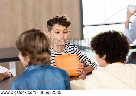 Selective Focus Of Schoolboy Opening Lunch Box While Sitting In School Eatery Near Classmates