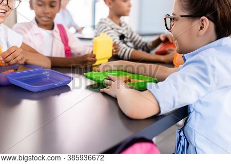Selective Focus Of Multiethnic Classmates Sitting In School Eatery Near Lunch Boxes
