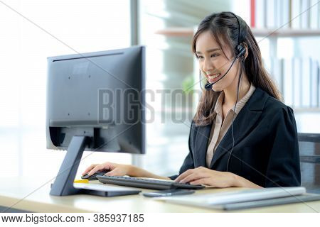 Asian Young Woman Working In Call Centre. Young Friendly Operator Woman Agent With Headsets Working