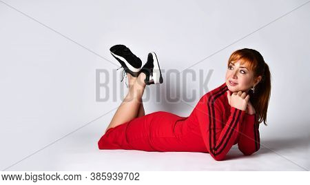 Cute Redhead Lady In A Red Sports Dress And Black Sneakers. She Smiles, Touching Her Face And Lying