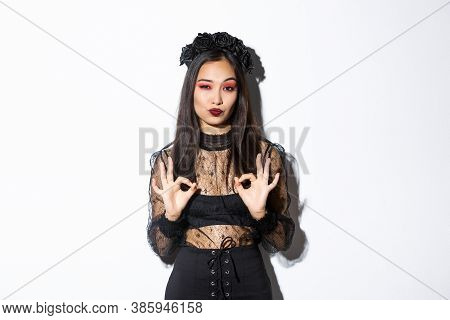 Image Of Stylish Asian Woman In Gothic Dress, Looking Satisfied And Showing Okay Gestures In Approva
