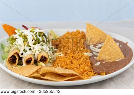 Taquitos Covered In Cheese With Rice And Beans Served On A Hot Plate For Some Delicious Mexican Food