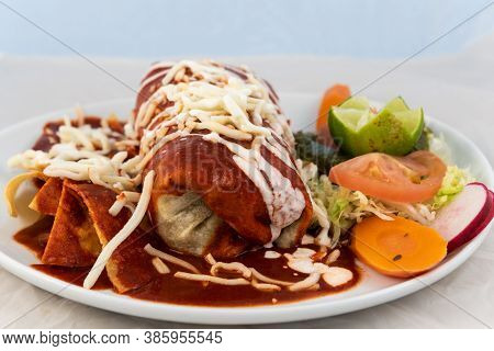 Wet Ranchero Burrito With Rice And Beans Served On A Hot Plate For Some Delicious Mexican Food.
