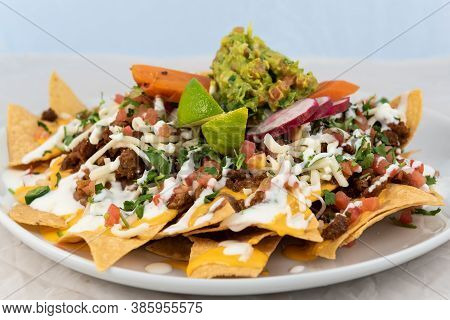 Large Stack Of Nachos Covered With Awesome Toppings Served On A Hot Plate For Some Delicious Mexican