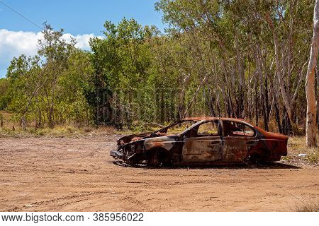 Rusting Wreck Of A Burnt Out Car Left Abandoned In Bushland With Most Of Its Parts Stolen