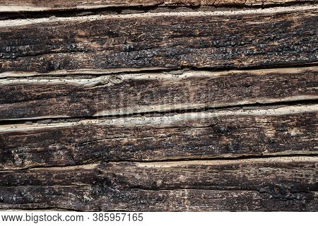 Background - The Texture Of Burnt Logs Of The Wall Of A Wooden House. Burnt Wood Charred Texture Of