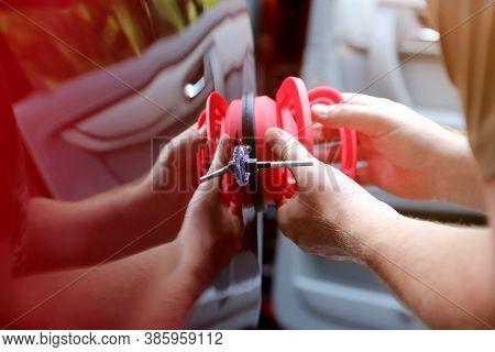 Man Fixing Car Dent By Himself. Repair Shop